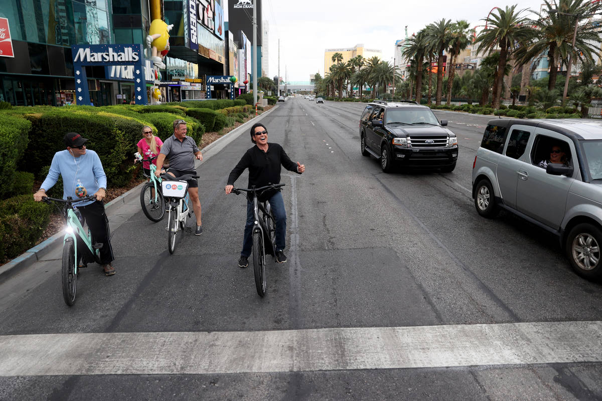 Mr. Las Vegas Wayne Newton, right, acknowledges fans while riding a bicycle on the Strip in Las ...