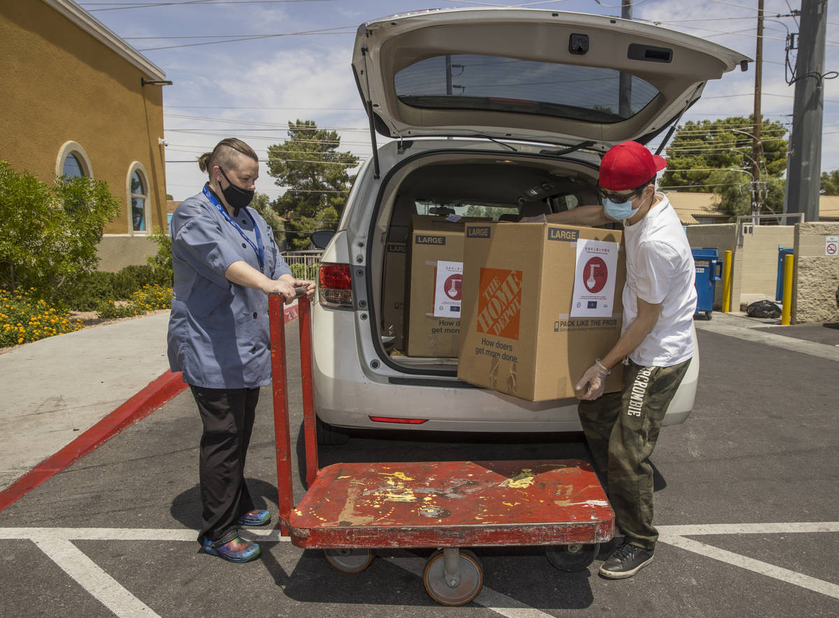Lindy Massey, left, with the Shannon West Homeless Youth Center holds a cart for China Mama Res ...
