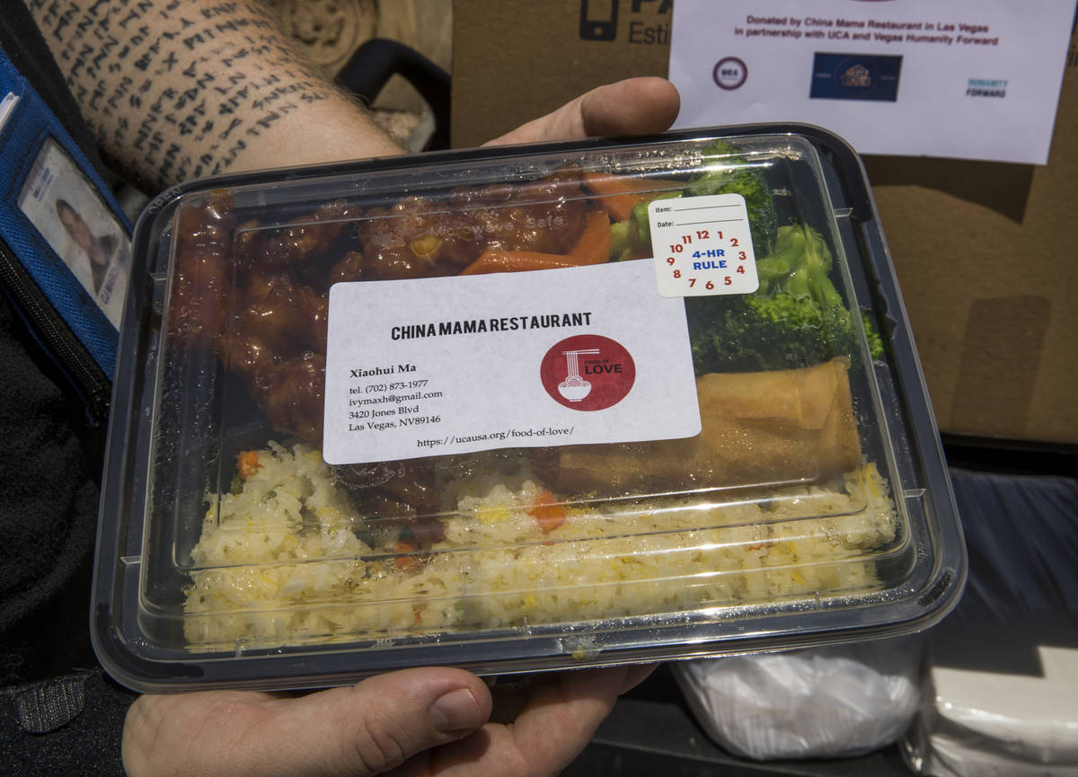 C.J. Marchand with the Shannon West Homeless Youth Center holds one of the freshly prepared don ...