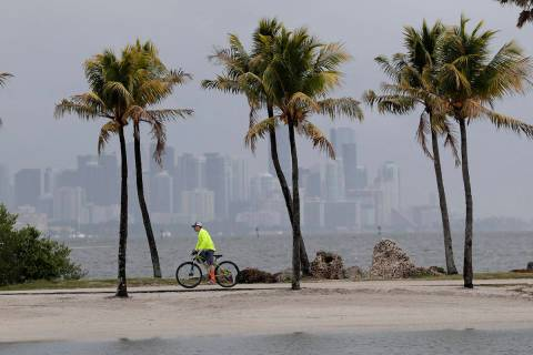 The Miami skyline is shrouded in clouds as a cyclist rides along Biscayne Bay at Matheson Hammo ...