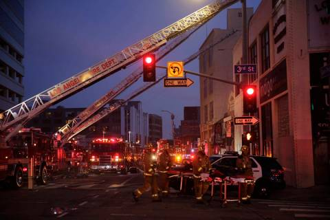 Los Angeles Fire Department firefighters work the scene of a structure fire that injured multip ...