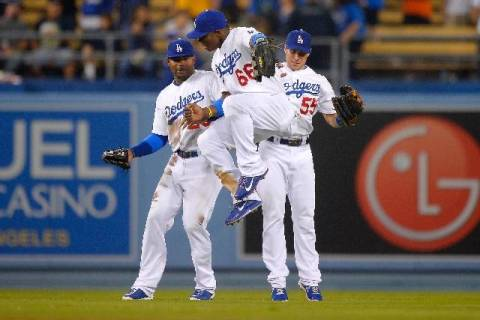 Dodgers outfielders Yasiel Puig (66), Skip Schumaker (55) and Carl Crawford celebrate Tuesday a ...