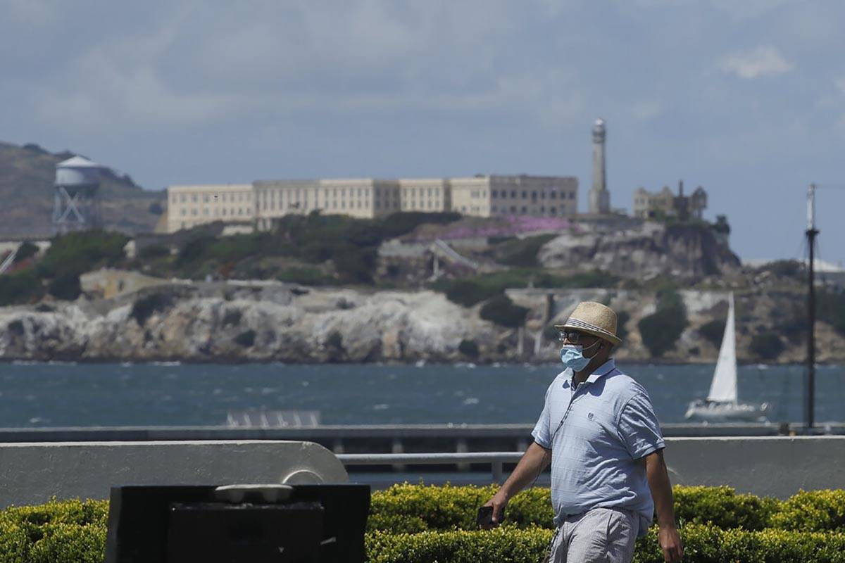 A man covers his face with a mask while walking on a path at Aquatic Park in front of Alcatraz ...