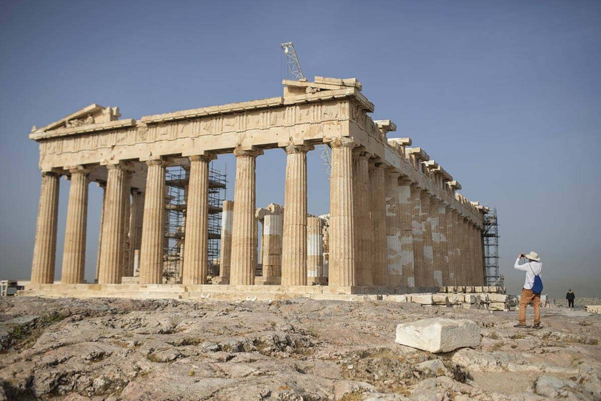 A man takes a picture next the ancient Parthenon temple at the Acropolis hill of Athens, on Mon ...