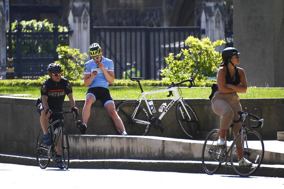 Cyclists wait at Parliament Square, in London, Monday, May 18, 2020. Large areas of London are ...
