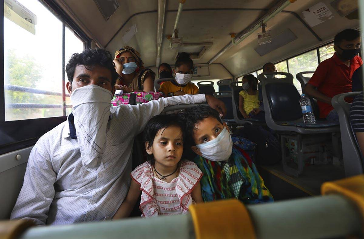 A migrant family from another state trying to return to their villages waits in bus to be trans ...