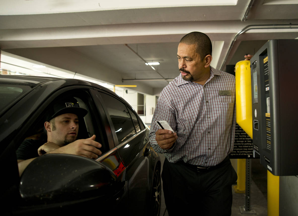 Jeff Carbullido helps a visitor exit the parking garage on the first day of paid parking at the ...