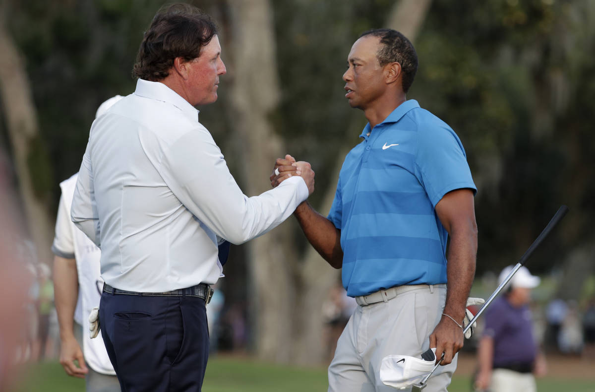 In this May 10, 2018, file photo, Phil Mickelson, left, and Tiger Woods shake hands after the f ...