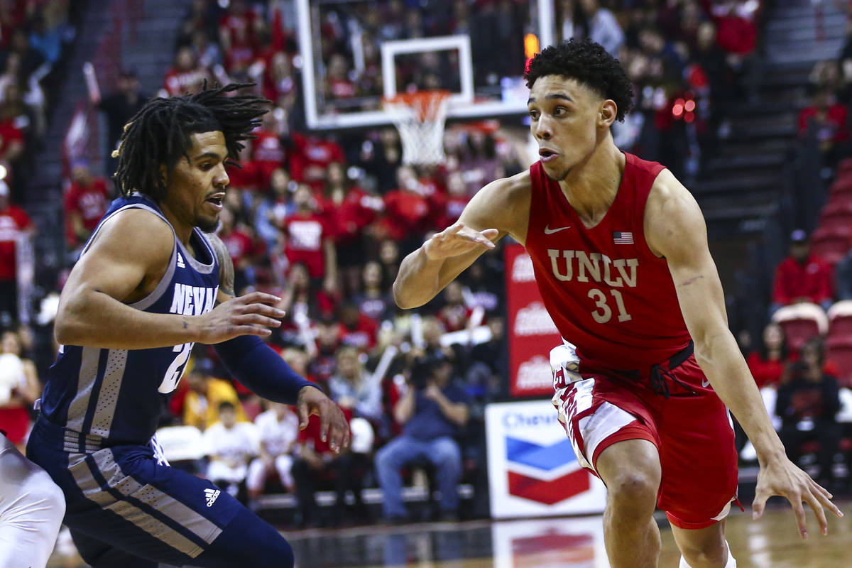 UNLV's Marvin Coleman (31) drives to the basket against UNR's Jazz Johnson (22) during the firs ...