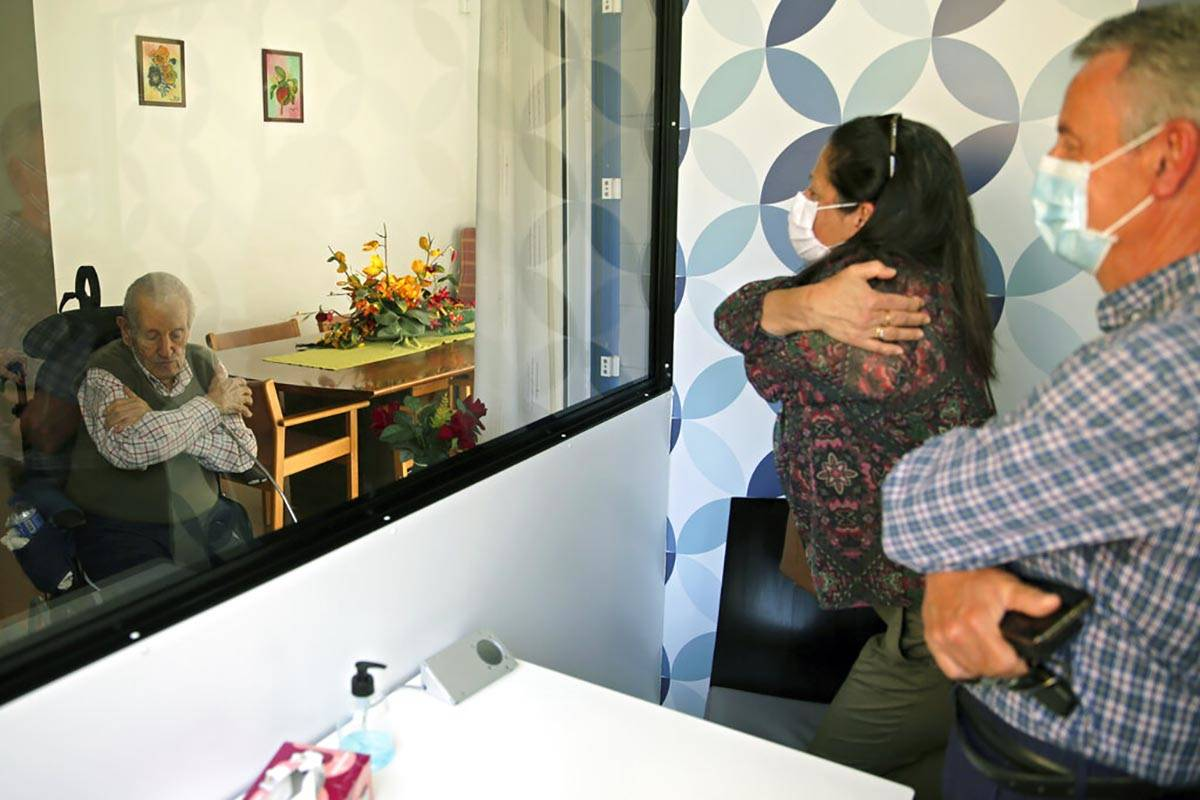Jose Gemas, 84, gestures a hug to his son Jose Navarro, right, and a family friend at the end o ...