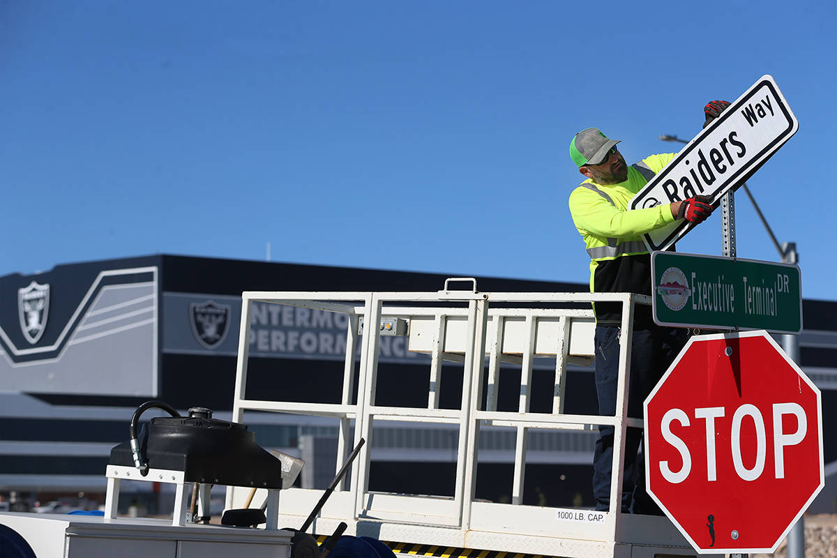 Kevin Weakland, signs and margins technician for the City of Henderson, installs a Raiders Way ...