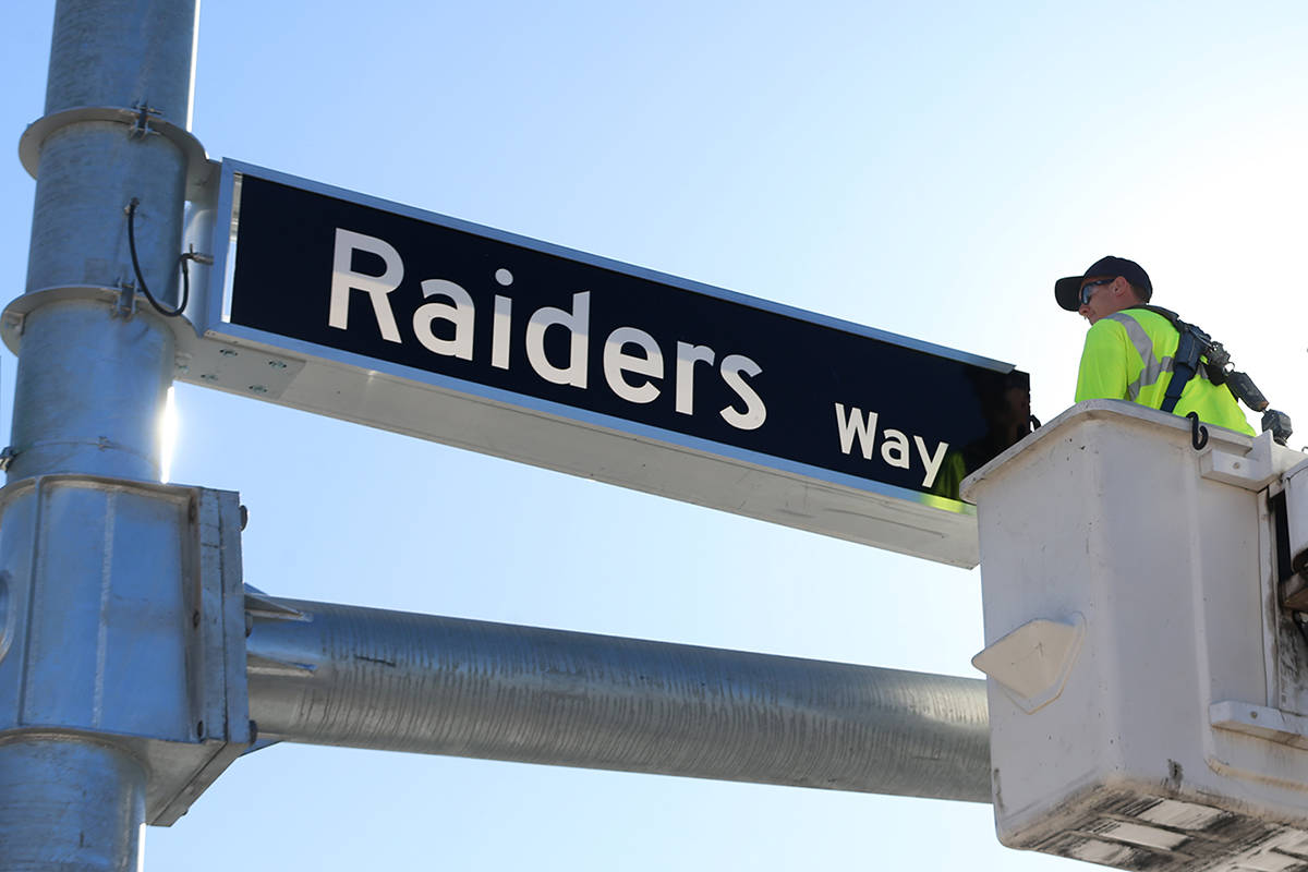 Justin Buhl, traffic signal technical for the City of Henderson, installs a Raiders Way street ...