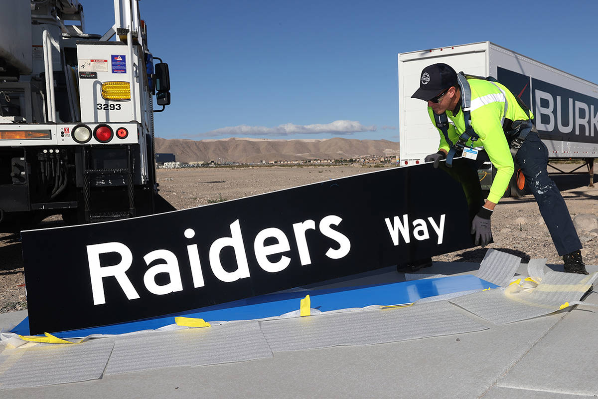 Justin Buhl, traffic signal technical for the City of Henderson, gets ready to install a Raider ...
