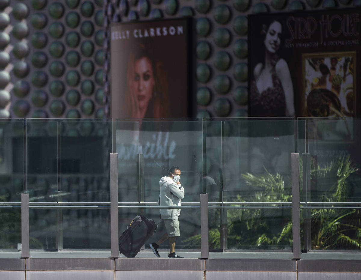 Tourists wearing medical masks make their way along the Strip on Tuesday, March 17, 2020, in La ...