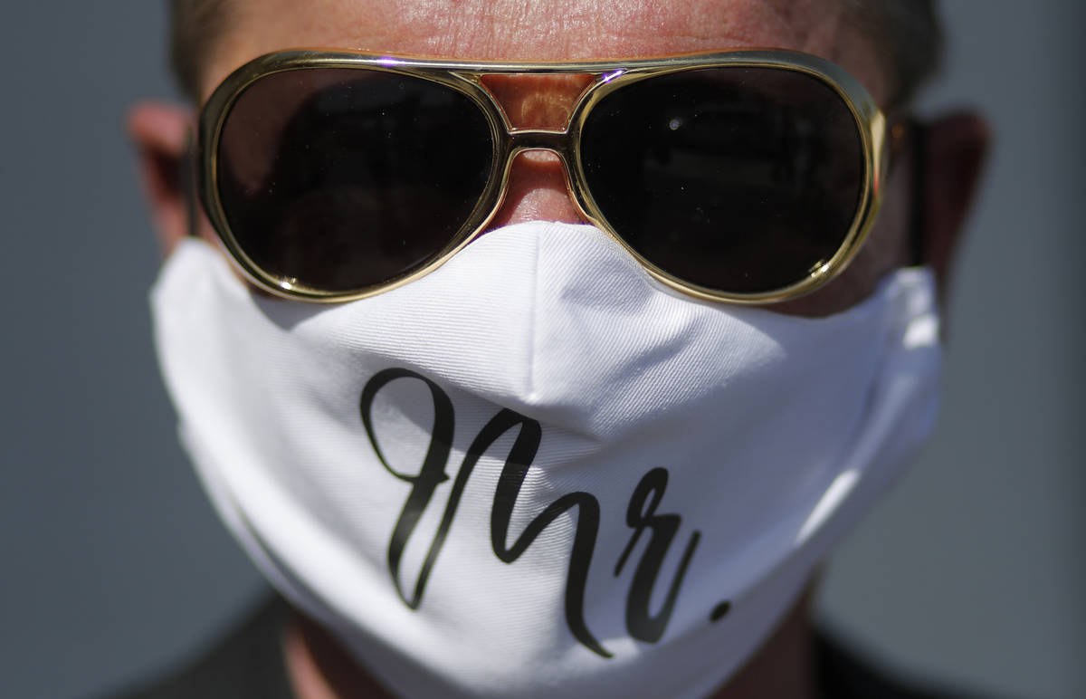 Vaughan Chambers wears a mask after marrying Alicia Funk at A Little Wedding Chapel, Tuesday, M ...