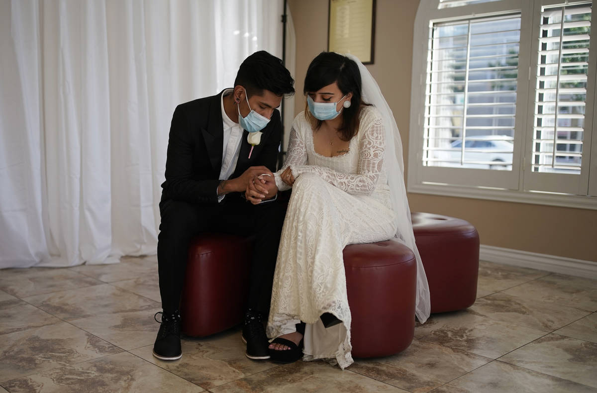 Angel Martinez, left, and Haillie Bernal hold hands while wearing masks as a precaution against ...