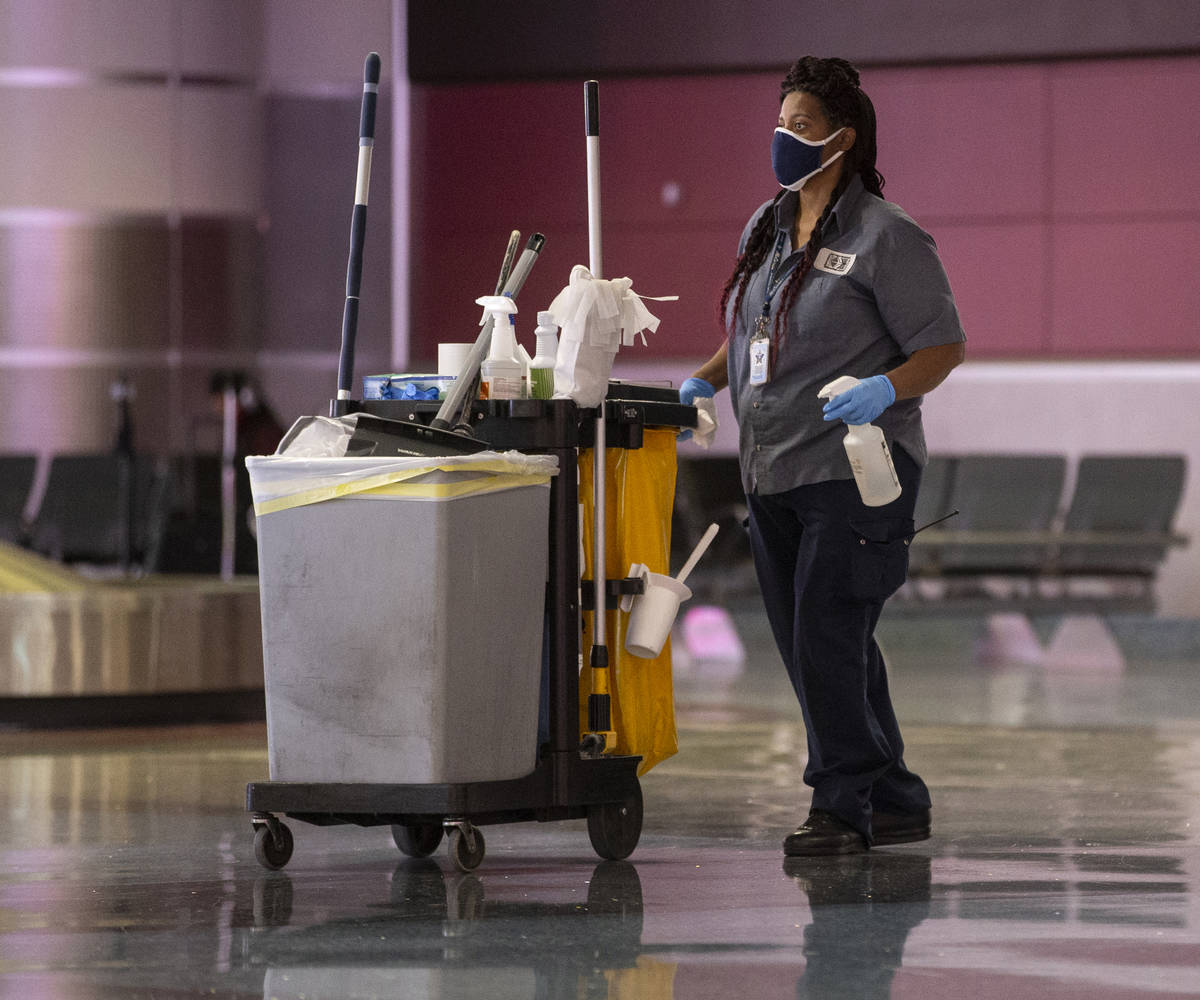 Cleaning staff work in the baggage claim area at McCarran International Airport on Wednesday, M ...