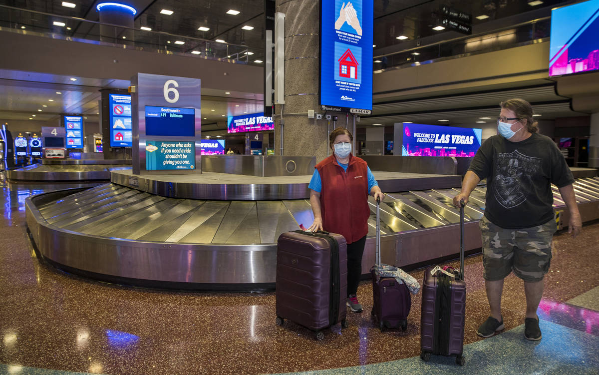 Susan Yowell and husband Jack gather her luggage after arriving at the Terminal 1 baggage claim ...