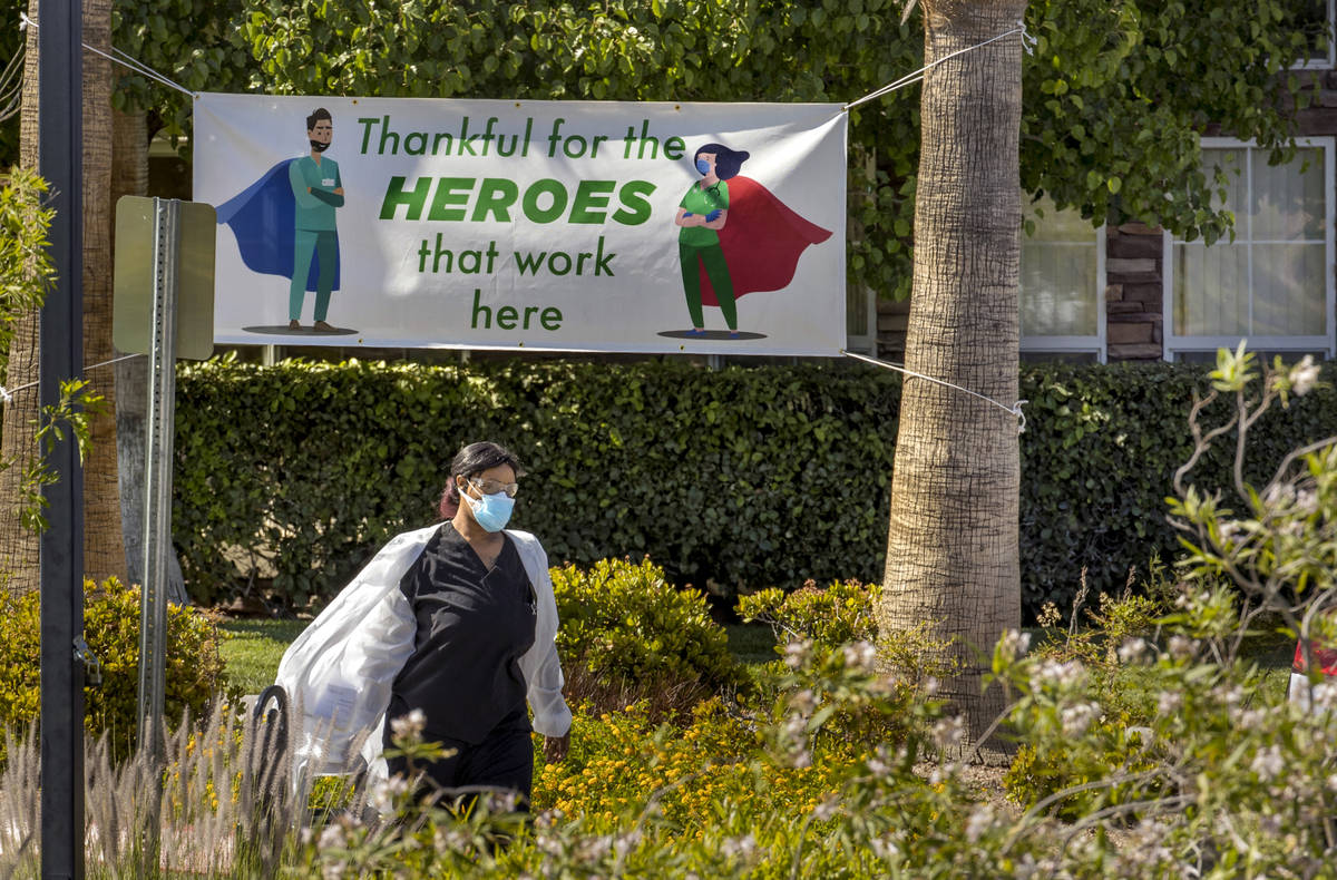A woman walks out of The Heights of Summerlin, which has had numerous deaths there due to COVID ...