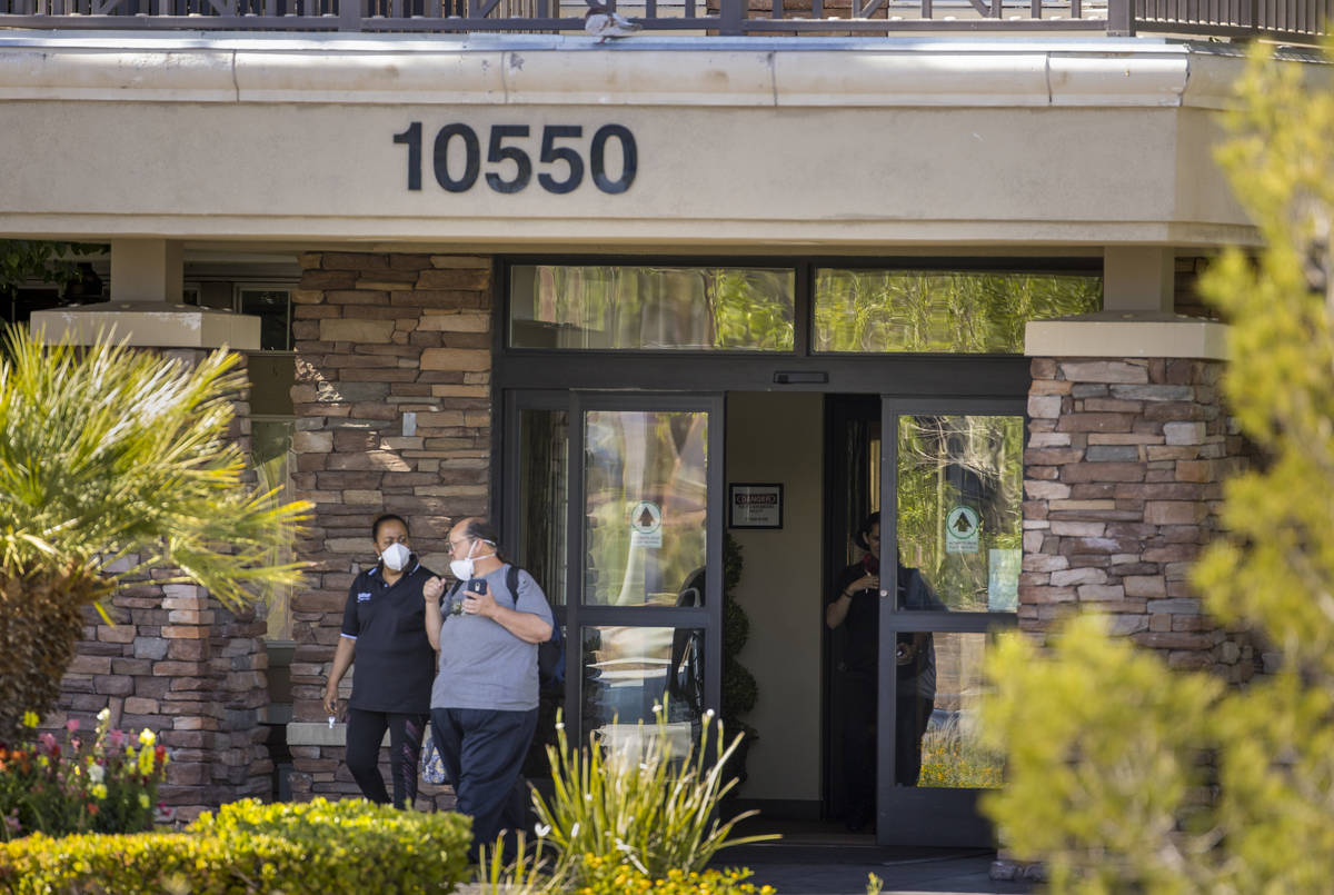 Two people walk out of The Heights of Summerlin which has had numerous deaths there due to Covi ...