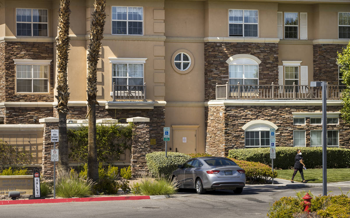 A woman walks outside of The Heights of Summerlin which has had numerous deaths there due to Co ...