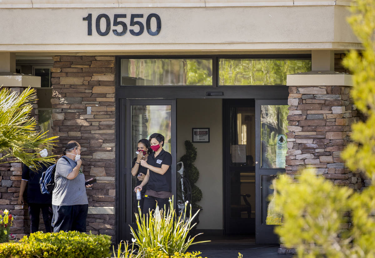 People walk out of The Heights of Summerlin, which has had numerous deaths there due to COVID-1 ...