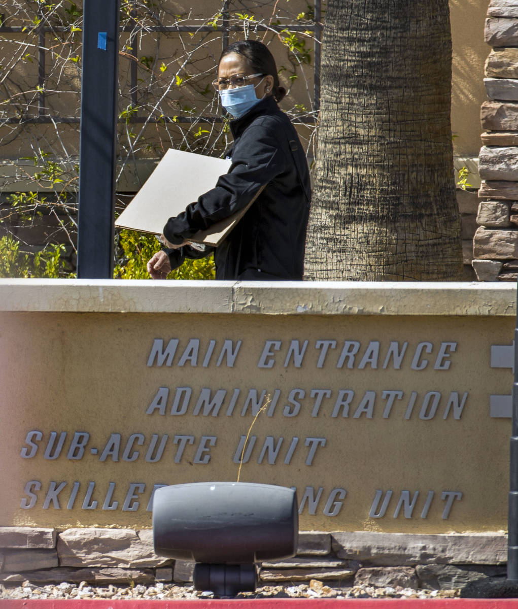 A woman walks outside of The Heights of Summerlin, which has had numerous deaths there due to C ...