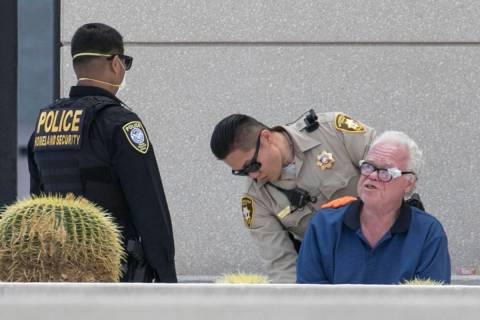 A man is detained as Las Vegas police investigate a report of a suspicious device outside the L ...