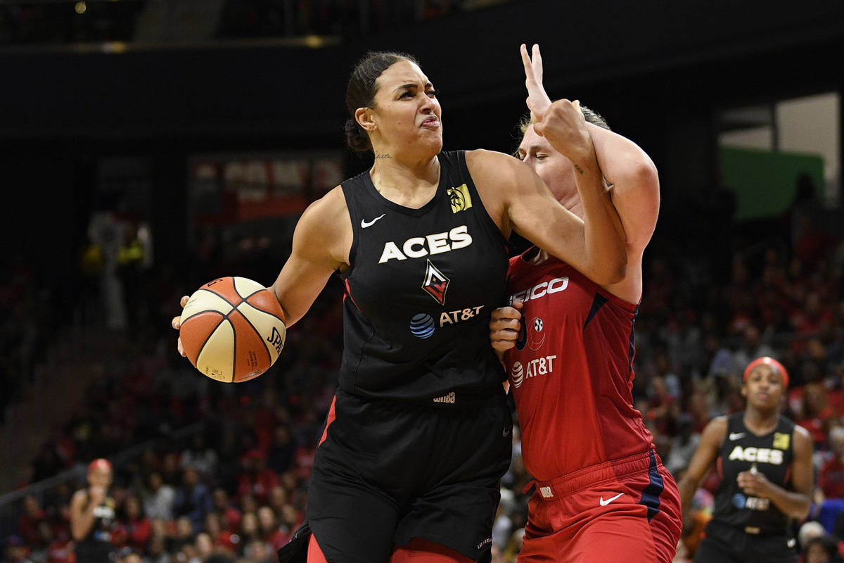 Las Vegas Aces center Liz Cambage, left, drives to the basket against Washington Mystics center ...