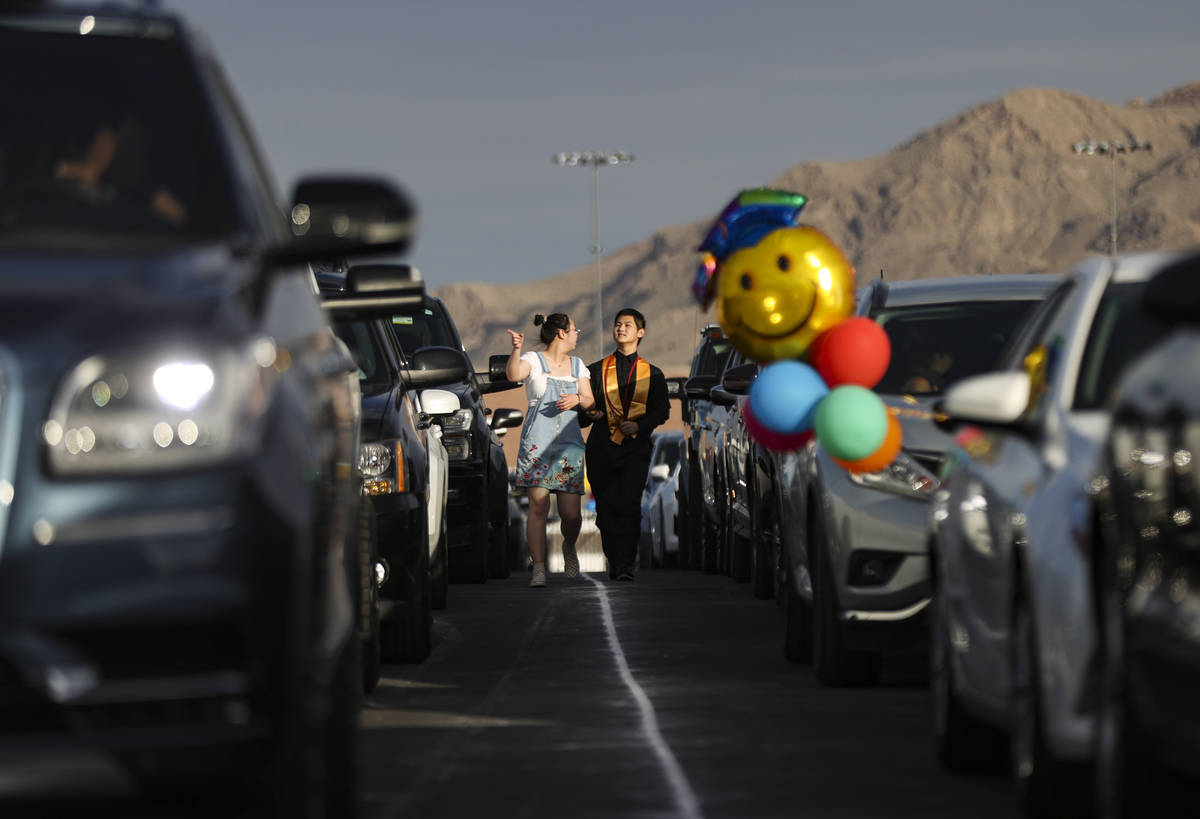 A Faith Lutheran High School student walks between cars before the start of a graduation ceremo ...