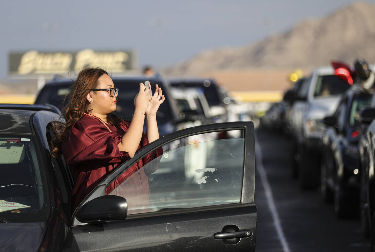 Faith Lutheran High School student Linh Tran takes a photo before the start of a graduation cer ...
