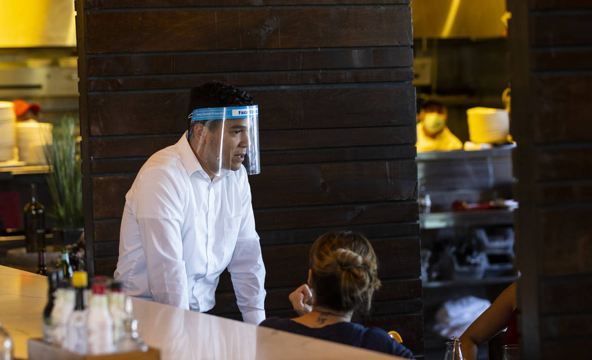 Ramon Mora wears a face shield while serving diners at Nora's Italian Cuisine in Las Vegas on T ...