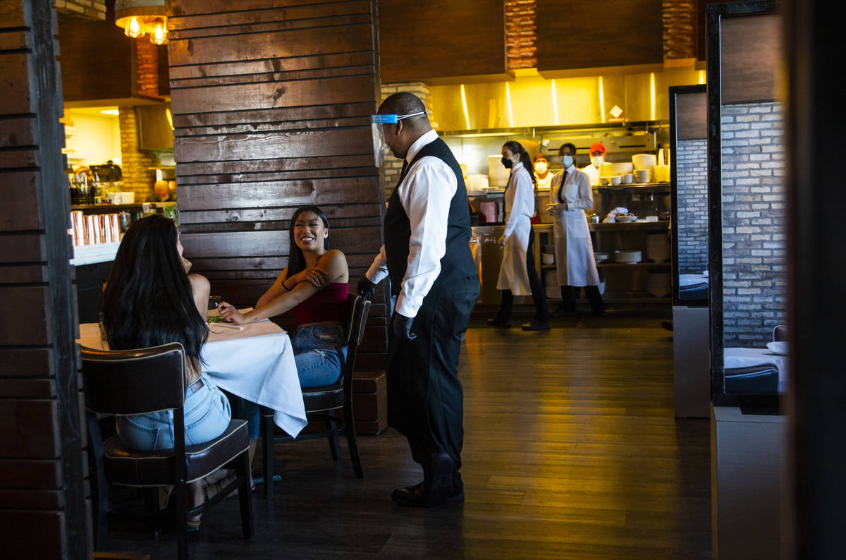 Diners Jasmin Montanez, left, and Juliana Asa talk with server Donald Bailey, wearing a face sh ...