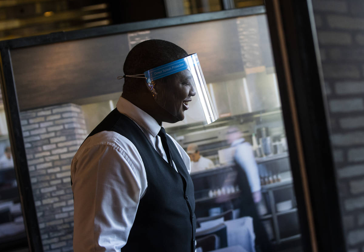Donald Bailey wears a face shield while serving diners at Nora's Italian Cuisine in Las Vegas o ...
