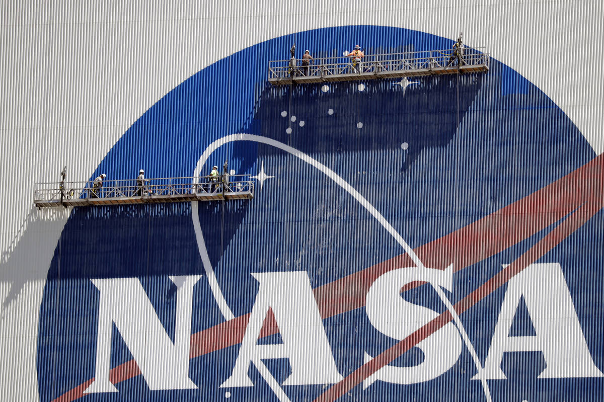 Workers near the top of the 526 ft. Vehicle Assembly Building at the Kennedy Space Center spruc ...