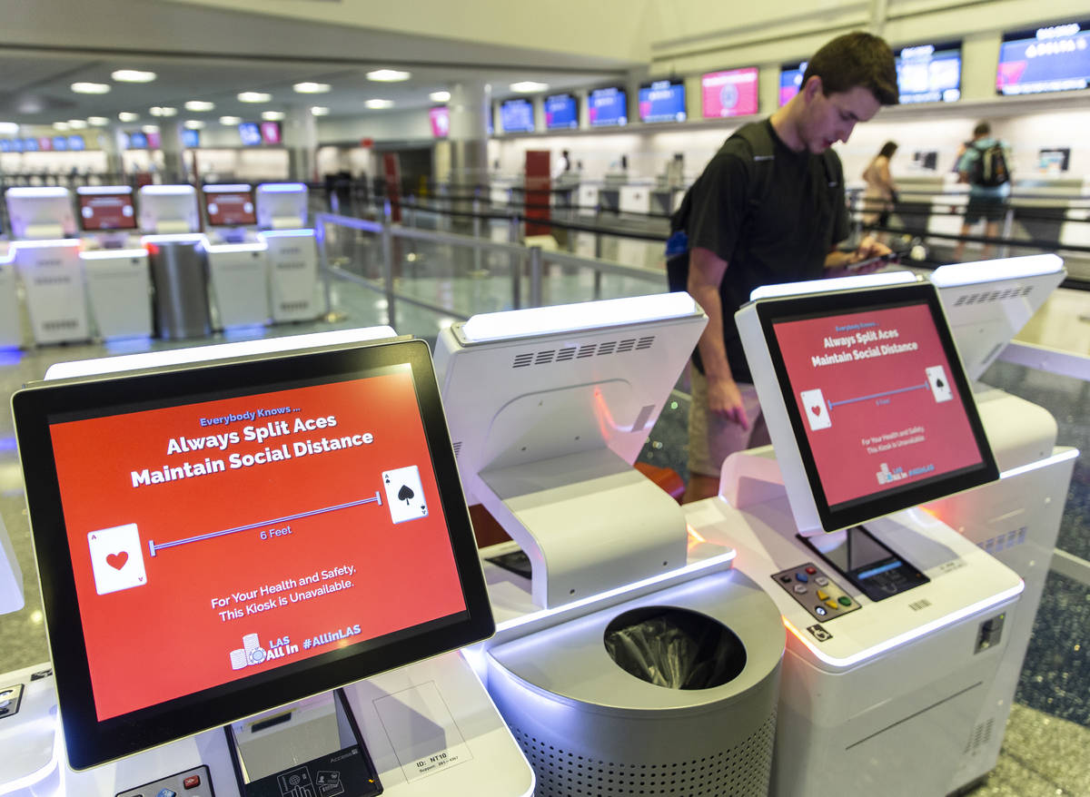 Travelers check in at newly arranged kiosks encouraging social distancing and outlining coronav ...