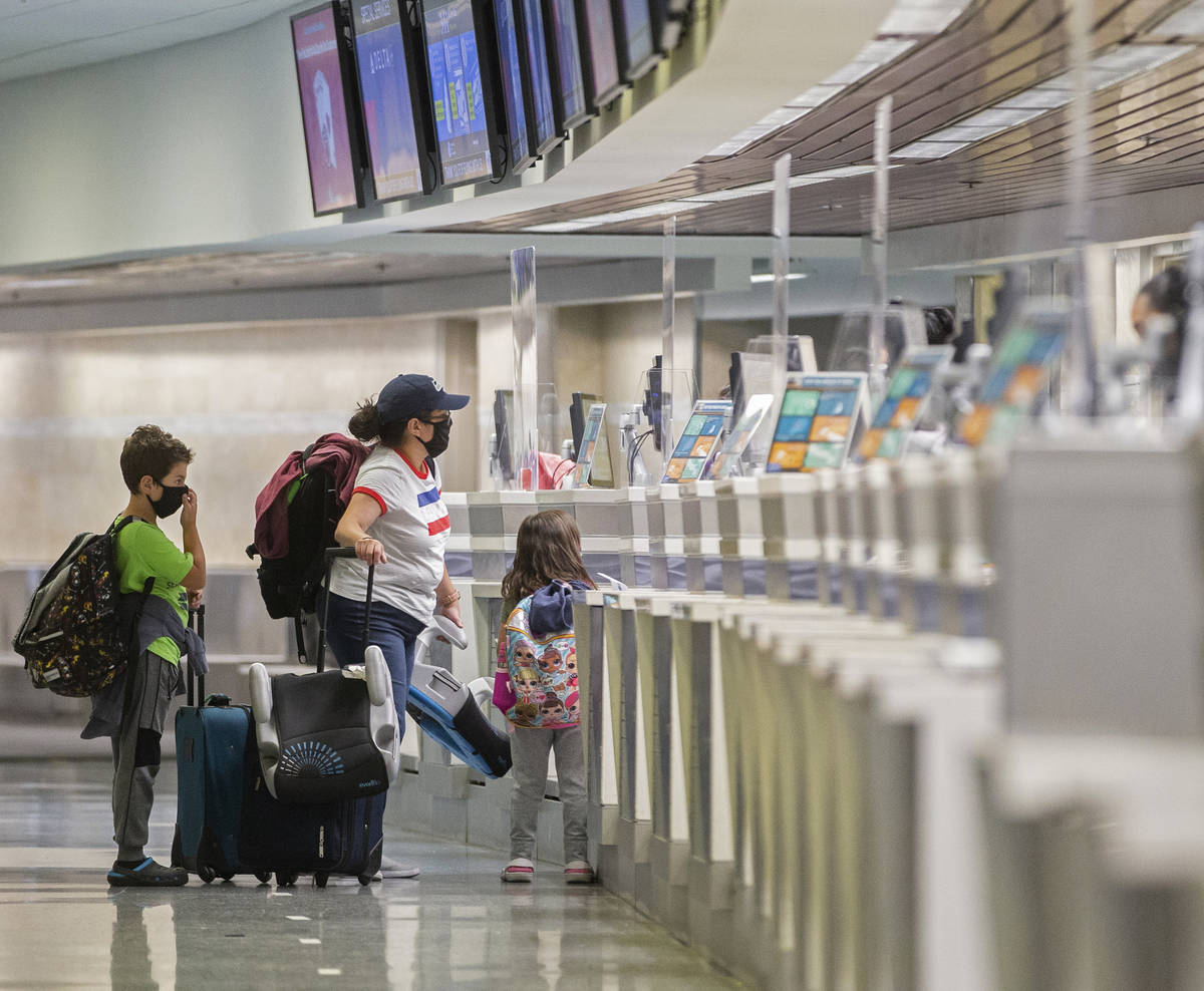 Travelers wearing medical masks check in at Delta Airlines in terminal one at McCarran Internat ...