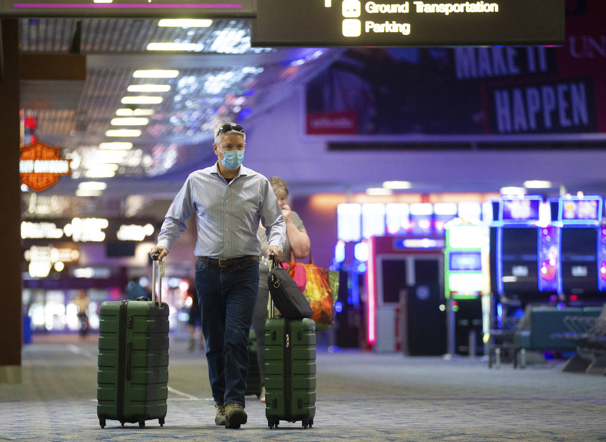 Travelers wearing protective masks make their way to their gate at terminal one at McCarran Int ...