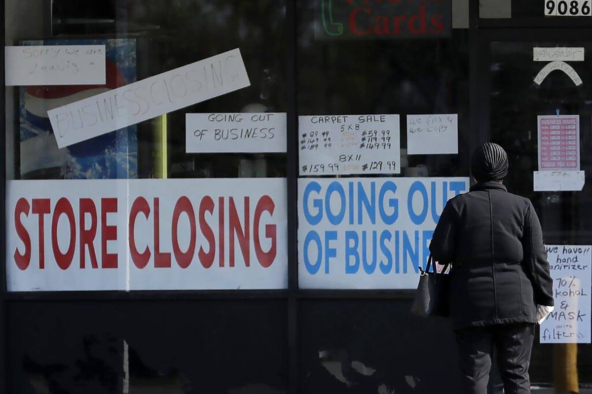 A woman looks at signs at a store closed because of the COVID-19 in Niles, Ill., on Wednesday, ...