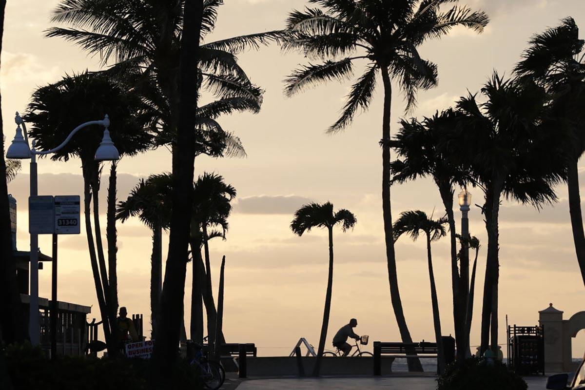 In this May 13, 2020 photo, a cyclist rides along the Hollywood Beach Broadwalk at sunrise duri ...