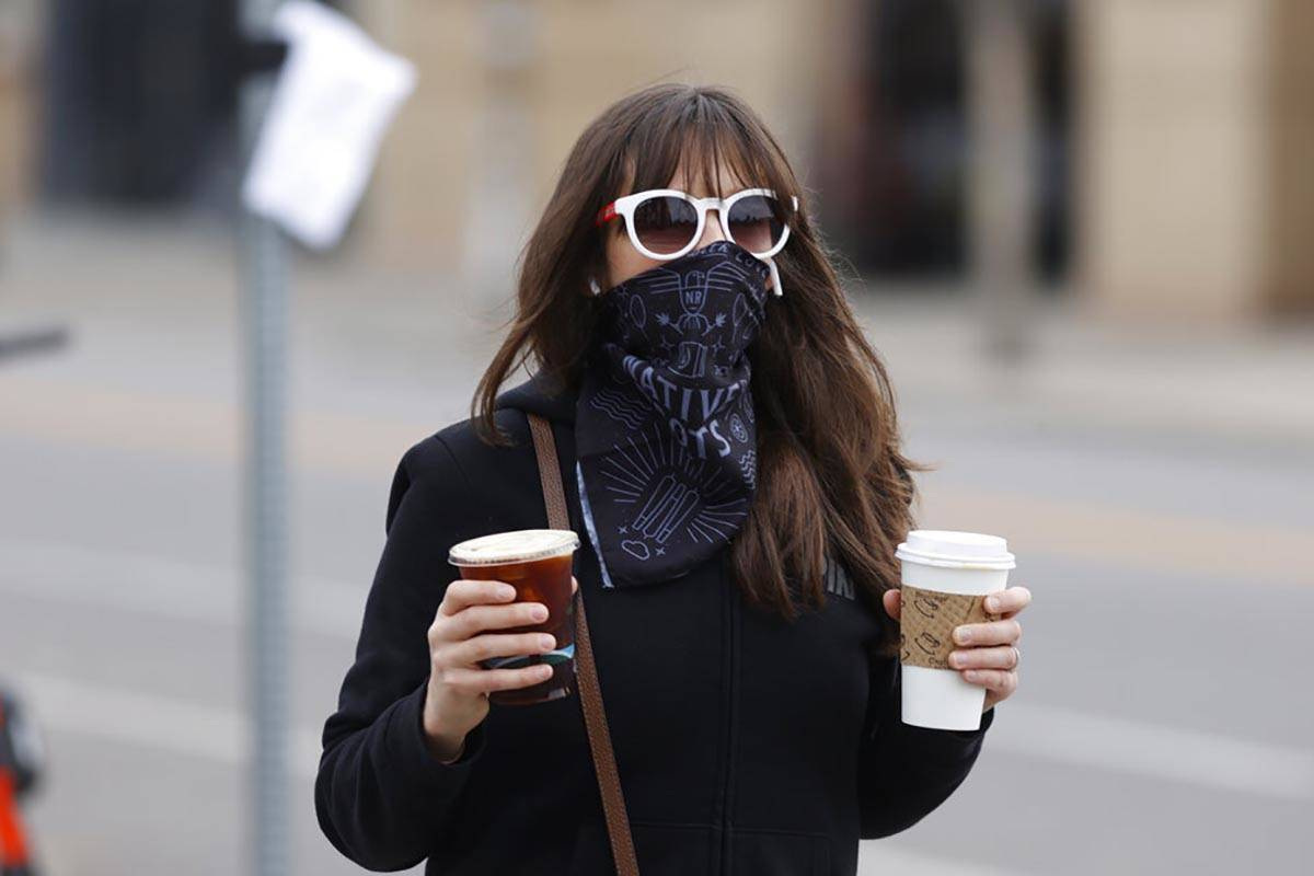 In this May 13, 2020 photo, a pedestrian wears a face mask while carrying drinks from a nearby ...
