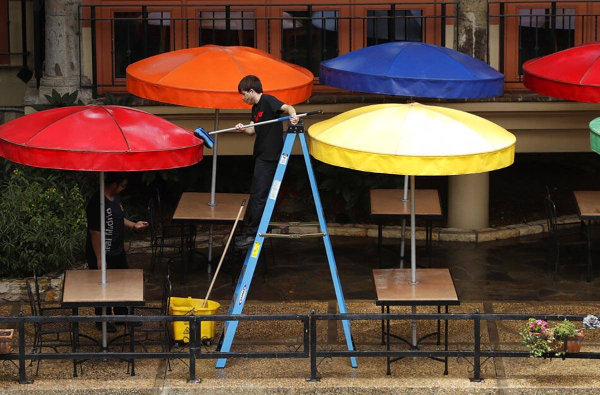 In this May 13, 2020 photo, a worker cleans umbrellas at a restaurant along the River Walk that ...