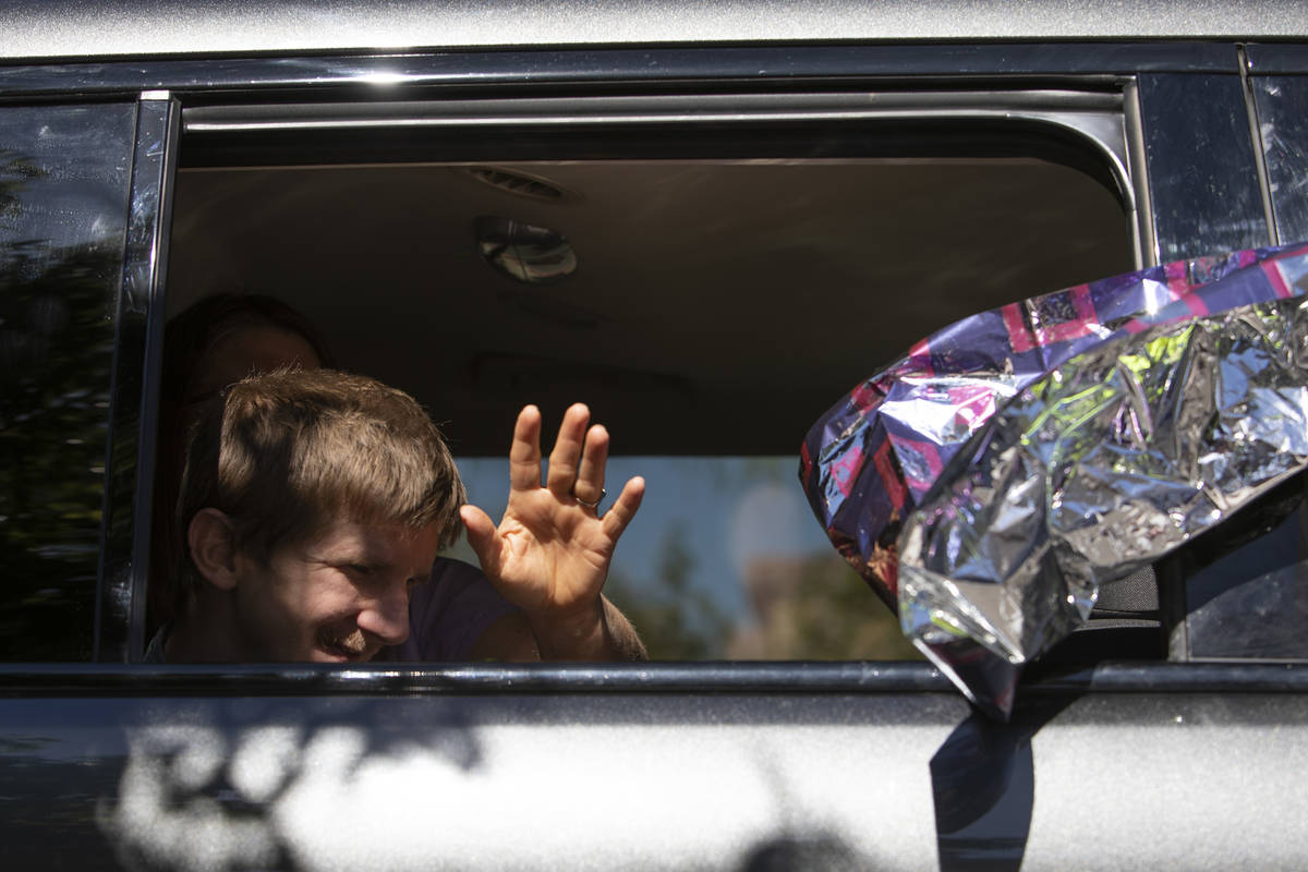 An Opportunity Village client and their family waves to staff members at Opportunity Village Ra ...