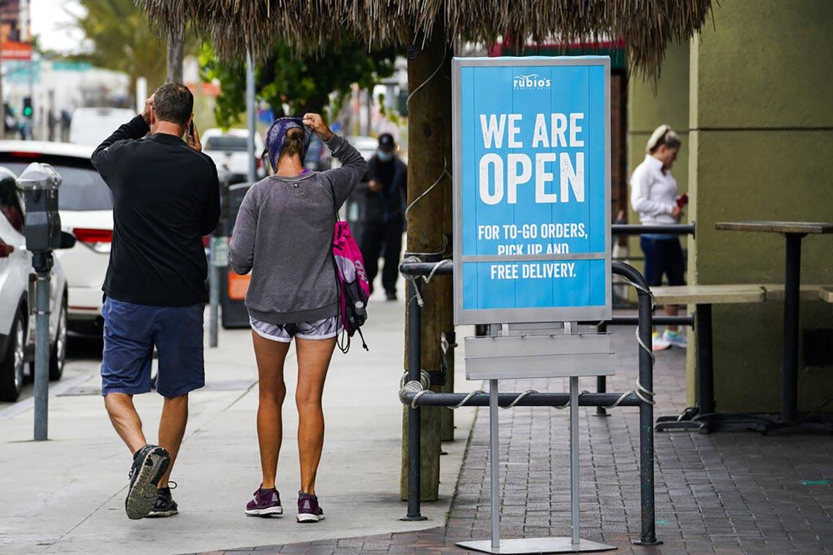 In this May 12, 2020 photo, customers walk past an open sign at Rubio's Coastal Grill on Tuesda ...