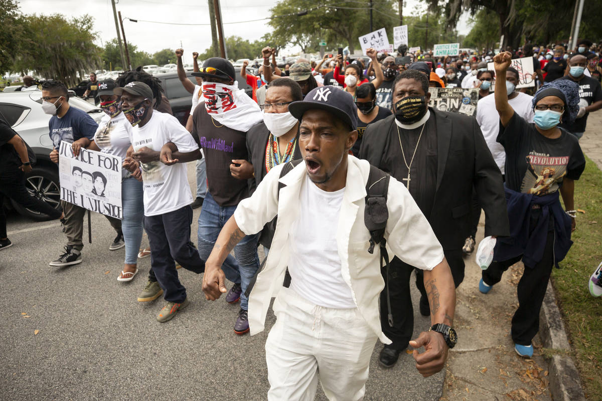 Malik Muhammad, center, joins a group of people marching from the Glynn County Courthouse in do ...