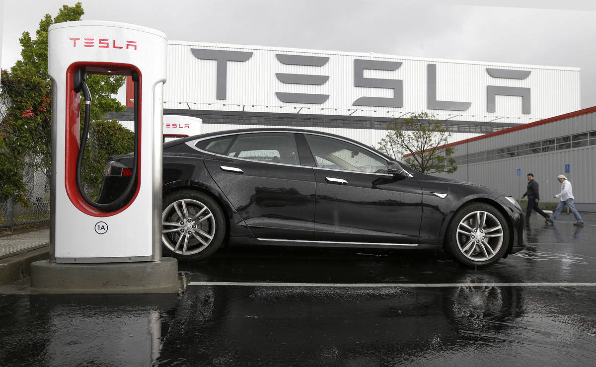 FILE - In this May 14, 2015, file photo, a Tesla vehicle is connected to a Tesla charging stati ...