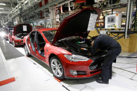 FILE - In this May 14, 2015, file photo, Tesla employees work on a Model S cars in the Tesla fa ...