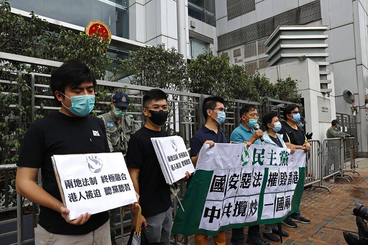 Members of the Democratic Party hold banner and placards during a protest in front of the Chine ...