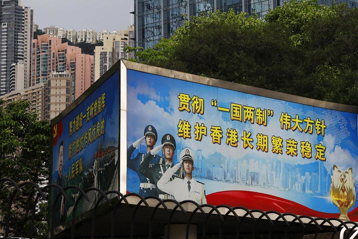 "The billboard which reads ""Implement the great policy of 'One Country, Two Systems', maint ..."