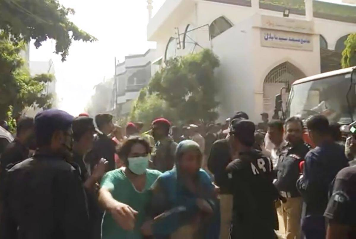 In this image made from video, crowds gather at scene of plane crash near Karachi, Friday, May ...